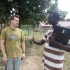 """Juba Arabic on the path lesson 42"" with Pastor John (aka Waldo, because we see him everywhere we go!)... We are standing near the clinic, with our fence/house/water tower visible in the background.  Note also the slasher in Jeff's hand."